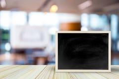 在桌上的空白的黑板在有bokeh的迷离餐馆 免版税图库摄影