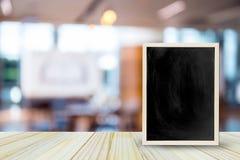 在桌上的空白的黑板在迷离餐馆有bokeh背景 库存照片