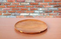 在桌上的空的圆的木盘子在砖墙背景 免版税库存图片