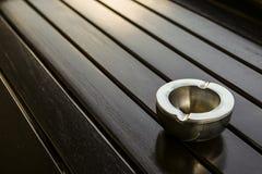 在桌上的空的金属烟灰缸 免版税库存图片