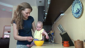 在桌上的粗心大意的保姆妇女饲料婴孩在厨房里 4K 股票录像