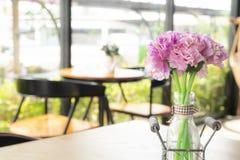 在桌上的紫色人造花在咖啡馆 免版税库存图片