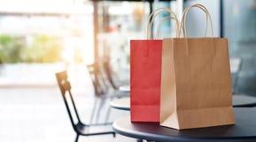 在桌上的红色和棕色购物袋在前边购物中心 图库摄影