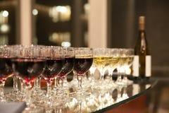 在桌上的红色和白葡萄酒 免版税库存照片