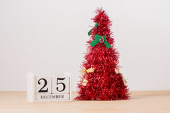 在桌上的红色圣诞树与日历12月25日 库存照片