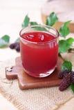 在桌上的红色桑树汁 免版税库存照片