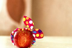 在桌上的红色苹果与一把逗人喜爱的绷带弓 库存照片