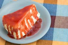 在桌上的绉纱蛋糕或牛奶蛋糕倾吐的草莓酱顶部 库存照片