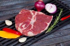 在桌上的美丽和水多的未加工的牛排与准备好的成份烤 免版税库存照片