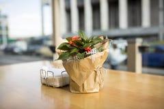 在桌上的美丽的花在咖啡馆 背景城市晚上街道 库存照片