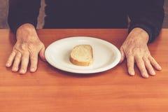 在桌上的老人的手与一片面包片在中部 免版税库存照片