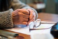 在桌上的老人` s手在玻璃旁边 图库摄影