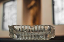 在桌上的老玻璃烟灰缸在迷离墙壁背景,葡萄酒,黑暗,拷贝空间 免版税库存图片