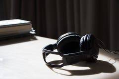 在桌上的耳机与阳光感受放松 库存图片
