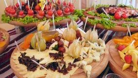 在桌上的肉、菜和chees快餐 重点玻璃表婚礼 自助餐干酪快速鱼粉表 股票视频