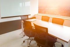 在桌上的膝上型计算机在空的公司会议室有在背景的都市风景视图 库存照片