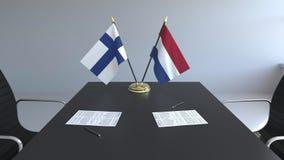 在桌上的芬兰和荷兰的旗子和纸 交涉和签署一项国际协定 皇族释放例证