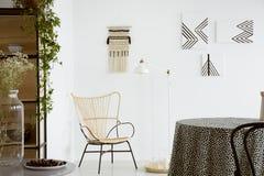 在桌上的花在明亮的公寓内部的现代扶手椅子附近与灯和海报 实际照片 免版税图库摄影