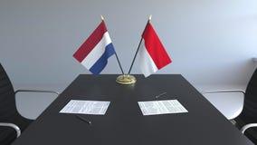 在桌上的荷兰和印度尼西亚的旗子和纸 交涉和签署一项国际协定 皇族释放例证