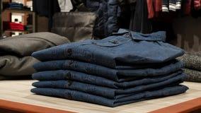 在桌上的蓝色牛仔布衬衣在服装店 图库摄影