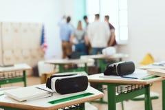 在桌上的虚拟现实耳机与站立老师和高中的学生后边 免版税库存图片