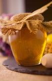在桌上的蜂蜜瓶子 免版税库存图片