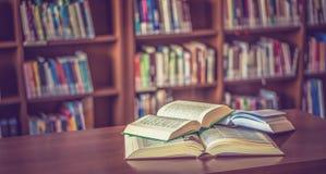在桌上的被打开的书在图书馆里 免版税库存照片