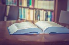 在桌上的被打开的书在图书馆里 库存照片