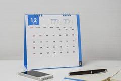 在桌上的被隔绝的12月日历与智能手机和笔 库存照片
