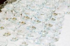 在桌上的许多空的香槟玻璃在餐馆 免版税库存照片