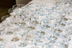 在桌上的许多空的香槟玻璃在餐馆 库存图片