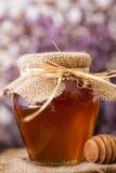 在桌上的金黄甜蜂蜜瓶子 库存图片