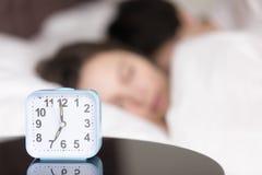 在桌上的闹钟在睡觉年轻夫妇前面 库存图片