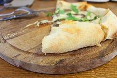在桌上的静物画在一个咖啡馆用在一个木板的比萨和与刀子的一把叉子 图库摄影
