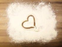 在桌上的面粉与心脏 免版税库存照片