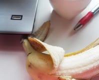 在桌上的香蕉与计算机和红色笔 图库摄影