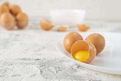 在桌上的鸡蛋与破裂在一半一个,卵黄质和蛋白质在被打开的鸡蛋,炒蛋cookings 免版税图库摄影