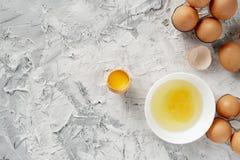 在桌上的鸡蛋与破裂在一半一个,卵黄质和蛋白质在被打开的鸡蛋,炒蛋cookings 免版税库存照片