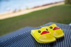 在桌上的黄色凉鞋鸭子在游泳池旁边 免版税库存照片