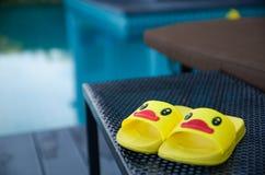 在桌上的黄色凉鞋鸭子在游泳池旁边 免版税图库摄影
