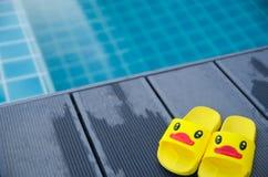 在桌上的黄色凉鞋鸭子在游泳池旁边 免版税库存图片