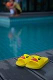 在桌上的黄色凉鞋鸭子在游泳池旁边 库存照片
