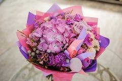 在桌上的紫色花花束构成 库存照片