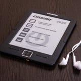 在桌上的EBook Digma和耳机 免版税库存照片