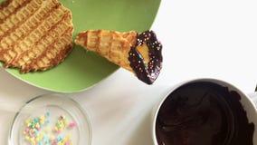 在桌上说谎在熔化巧克力浸洗的奶蛋烘饼锥体,并且用多彩多姿装饰洒 股票录像