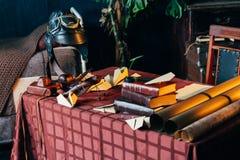在桌上说谎飞行员的盔甲、玩具飞机由木和自创飞机制成由纸制成和旧书,放大器 库存照片