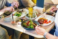 在桌上,两个人吃晚餐,吃一块牛排,用在一块白色板材的沙拉,有一把叉子和刀子的在他们的手上 免版税库存图片