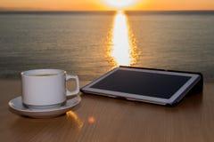 在桌书桌上的白色片剂ipad有在日落期间的咖啡杯的,当太阳反射在水 图库摄影
