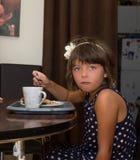 在桌后的小女孩就座 免版税库存照片