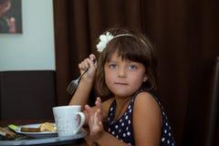 在桌后的小女孩就座 免版税图库摄影